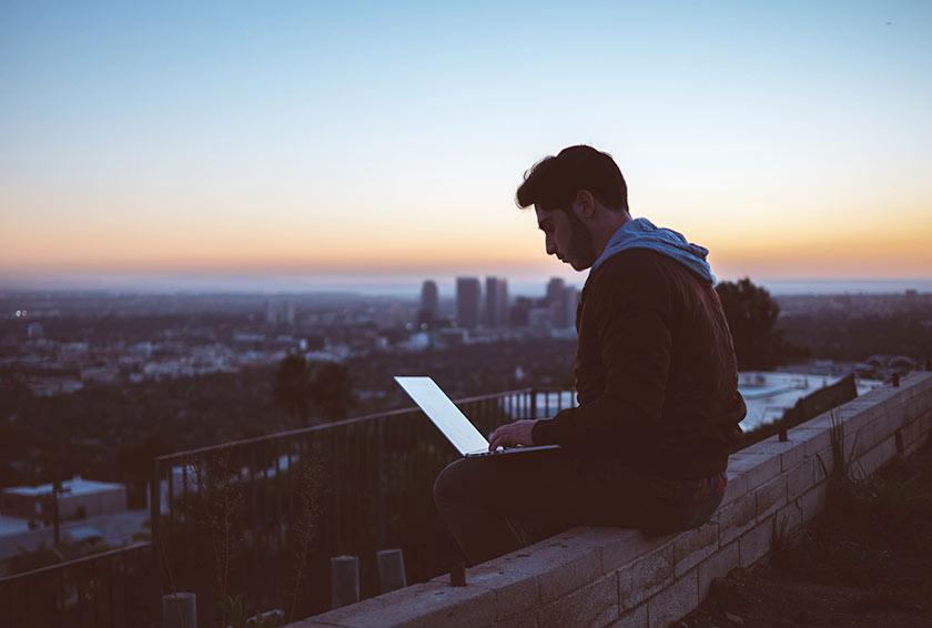 IT-Infrastruktur Teil 1 - Internet, Bandbreite, E-Mail - junger Mann sitz am dach mit Laptop