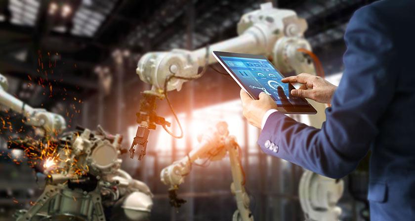Was sind Managed Services? - Mann mit Tablet steuert Industrieroboter